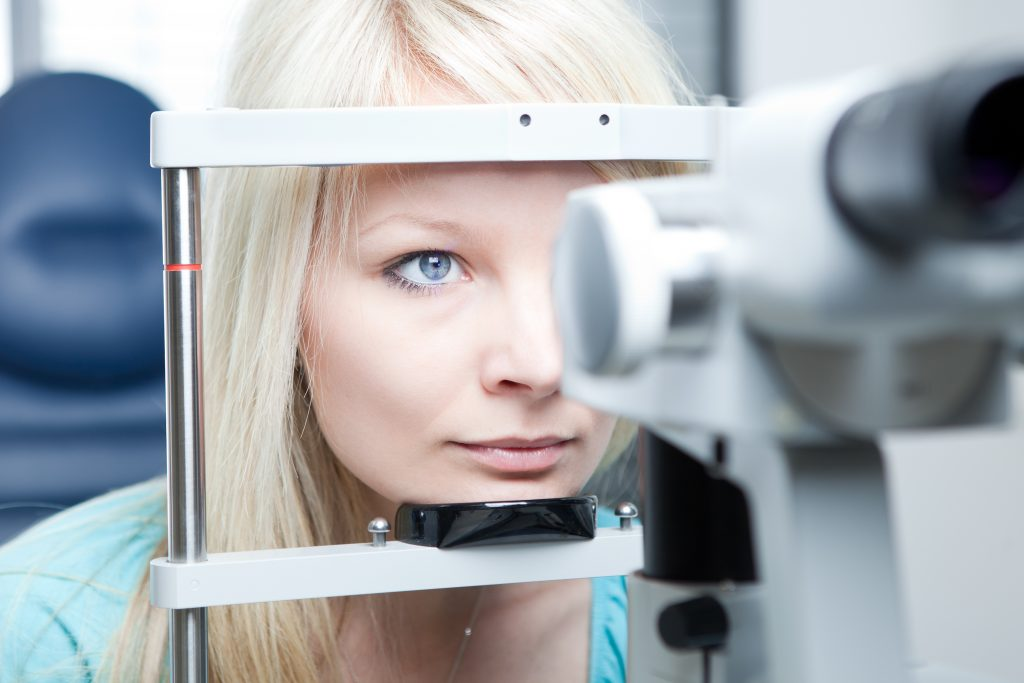 pretty young woman having her eyes examined by an eye doctor on a slit lamp