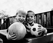 Image of two boys holding sports balls in black and white