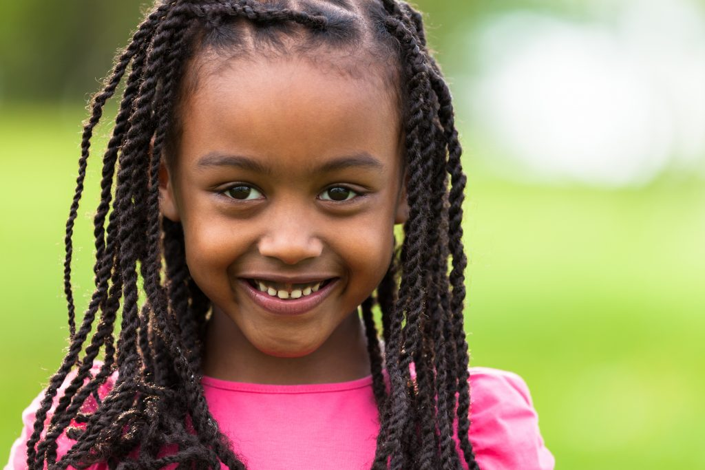 Outdoor close up portrait of a cute young black girl smiling